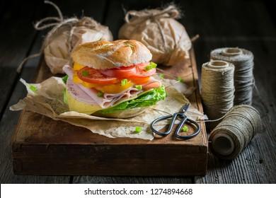 Take away sandwich packed in gray paper in dark mood