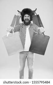 Take bags, its Black Friday. Happy hipster in bull horns hat holding shopping bags. Bearded man smiling with paper bags after seasonal sale. Carrying purchases in colorful non grocery carrier bags.