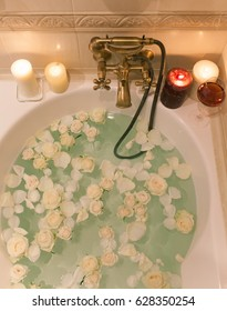Take a bath with rose petals and candles. Romantic evening in the bathroom with wine and candles
