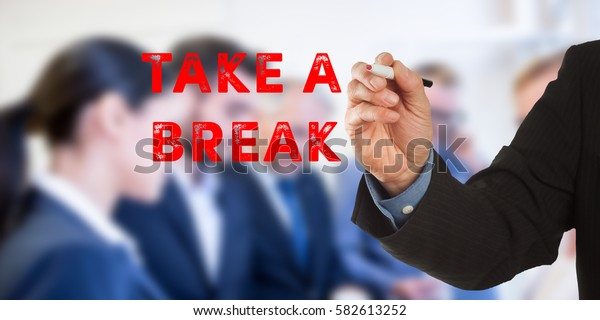 Take a break, Male hand in business wear holding a thick pen, writing on an imaginary screen at the camera, business team in background, digital composing.
