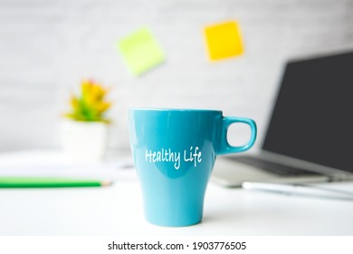 Take Care for healthy life office.  Close Coffee blue cup for relax and take a break supplies and laptop background.  Lifestyle Health Concept