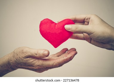 take care of old mother - young female hand giving a red heart to old hand of a mother - happy mother's day