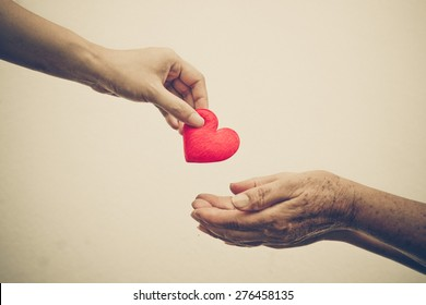 take care of old mother - young female hand giving a red heart to old hand of a mother