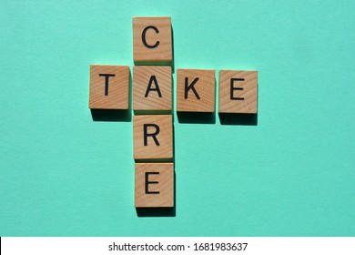 Take Care, in wooden letters on turquoise background with copy space