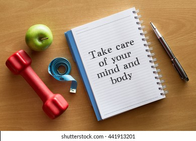 Take care of your mind and body advice or reminder - handwriting on notepad with dumbbell, green apple and measurement tape. Health and fitness concept.