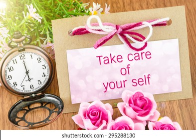 Take care of your self on tag and pocket watch with pink rose on wooden background.