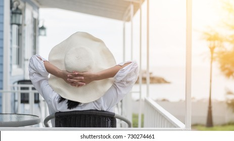 Take it easy lifestyle of carefree young woman wearing summer hat relaxing happily sitting on porch at beach-house on beach front enjoying healthy living life quality for holiday vacation concept