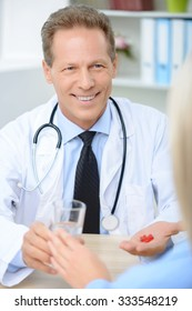 Take it every day. Vivacious  smiling professional doctor holding glass of water and pills giving them to his patient.