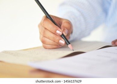 take the exam final high school university student holding pencil writing on paper answer sheet / education college in class taking notes sitting learning writing selected choice in examination room