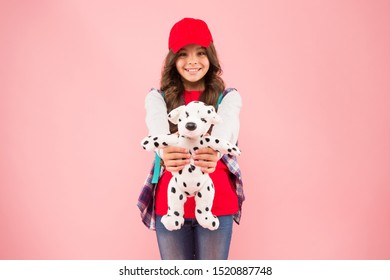 Take favorite toy with you. Reduce stress. Schoolgirl daily life. Schoolgirl street style clothes. School club. Stylish schoolgirl. Girl little fashionable cutie with backpack carry soft toy dog.