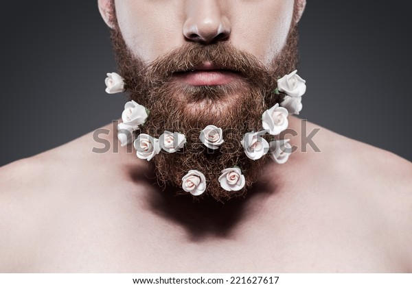 Take good care of your beard! Close-up of young shirtless man with flowers in his beard standing against grey background