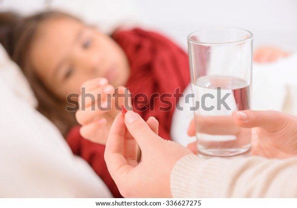Take it. Close up of red pill in hands of loving mother holding it and giving it to her daughter lying in bad