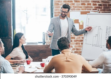 Take a look at our results! Handsome young man in glasses standing near whiteboard and pointing on the chart while his coworkers listening and sitting at the table