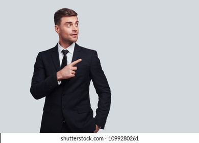 Take a look over there! Good looking young man in full suit pointing copy space and smiling while standing against grey background