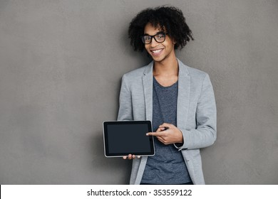 Take a look at this! Cheerful young African man looking at camera with smile and pointing on his digital tablet while standing against grey background