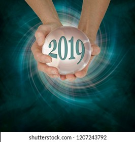 Take a look at what 2019 holds with a Crystal Ball Reading - female hands holding a large scrying ball containing the year 2019 against a deep green vortex spiral and copy space  below