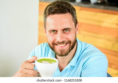 Take moment to care about yourself. Coffee drinkers live longer. Man bearded guy drinks cappuccino wooden table cafe. Cafe visitor happy smiling face enjoy coffee drink. Improve overall health.
