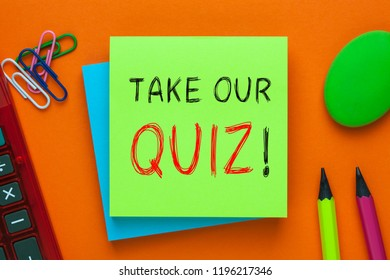 Take Our Quiz! written on green note with pencil and calculator a side. Motivational phrase.