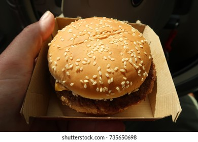 Take out container with a Cheeseburger on a sesame seed bun.