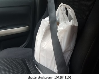 take out or pick up food plastic bag with a seat belt in a car seat