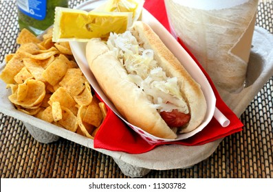 Take out tray with hot dog, drink and condiments.