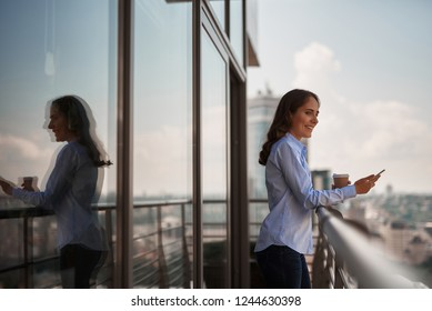 Take a pause. Portrait of smiling businesswoman enjoying city view with smartphone in hand while having coffee break on office balcony. Copy space on left