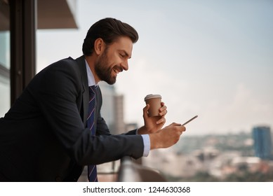 Take a pause. Waist up portrait of smiling businessman reading massages on smartphone while having coffee break on office balcony