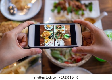 Take a photo of a smartphone for lunch or dinner. Woman taking picture with phone. Posting or sharing popular food for social media.