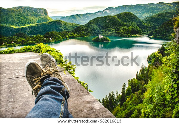 take a rest while hiking crossed feet lake aerial bled slovenia relax travel