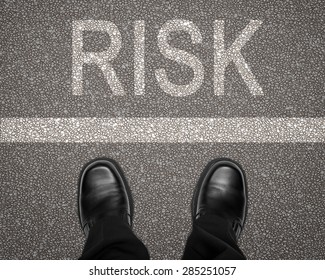 Take a risk concept with feet on road behind white line