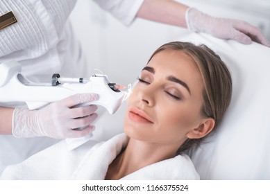 Take some rest. Close up portrait of smiling young lady with closed eyes having beauty procedure. She is lying on daybed at wellness center