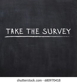 TAKE THE SURVEY hand writing chalk text on black chalkboard.