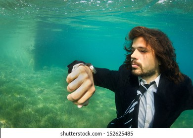 Take your business anywhere. Businessman Underwater watching time. Carpe Diem.