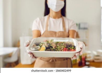 Takeaway cafe worker wearing medical face covering mask holding fresh healthy lunch in plastic food container ready for safe delivery. Concept of ordering meal, good service and taking care of clients