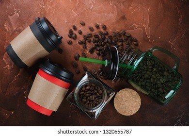 Takeaway carton and glass coffee cups with coffee beans. Flatlay on a fire-warm rusty metal surface
