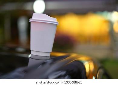 takeaway coffee cup put on black car road trips