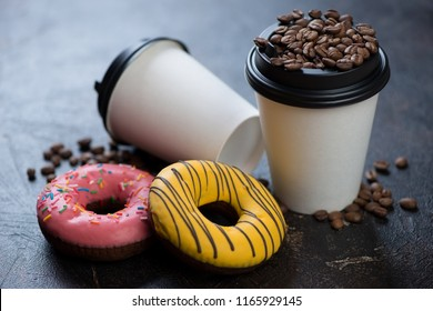 Takeaway coffee cups with donuts and coffee beans, studio shot on a dark brown stone background