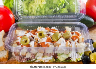 Takeaway salad with vegetables, toast, olives and dressing in a  transparent, disposable plastic box.
