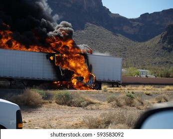 Taken in 2007, a semi-truck runs over a small car on Interstate Highway 10 in Arizona at Picacho Peak. The truck burst into flames because it was loaded with acid containers that ruptured.