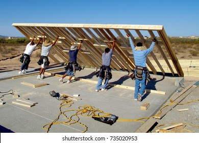 Taken in 2008. A group of construction workers raising a wood frame for a house located in Arizona. This was taken with their faces away from the camera because it was impossible to obtain a release.