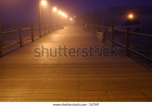 taken early morning at beach boardwalk light and morning fog