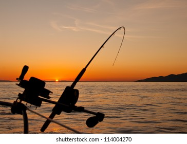 Taken just off the coast of Vancouver Island the silhouette of a down rigging fishing rod at sunset.