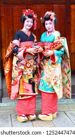 Taken on 1st April 2012 in Gion, Kyoto, Kansai, Japan. Two tourists dressed up in colourful traditional geisha costumes with kimonos, katsura and makeup in the old part of Gion, Kyoto.