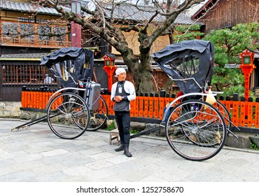 Taken on 1st April 2012 in Gion, Kyoto, Kansai, Japan. A Japanese rickshaw rider with two rickshaws against a background of old wooden buildings in Gion, the old part of Kyoto city.
