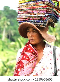 Taken on 20th September 2010 in Tegalalang, Bali, Indonesia. A woman selling batik sarongs in Tegalalang with her stock of sarongs piled up on her head.