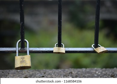 Taken on 21st August 2018 in Ashbourne Derbyshire U.K.  Color image of three personalised brass padlocks attached to railings.