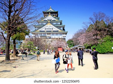 Taken on 5th April in Osaka, Kansai, Japan. View of Osaka Castle with a blue sky, sakura cherry blossom and some visitors in the foreground.