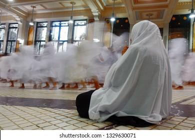 Taken on June 10 2018, a Muslim women praying while other pilgrims       (motion blur) performed  Saei between Safa and Marwa mount in Masjidil Haram Mosque, Mecca, Saudi Arabia
