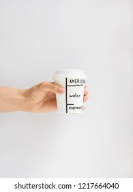 Take-out coffee cup Top view photo Woman is holding a paper cup with americano against white wall Recipe of Americano coffee