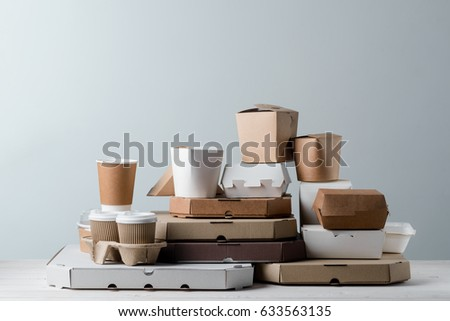 9bd238df4fd Take-out coffee cups in holders, pizza boxes and microwaveable paper food  containers, close-up. Light grey background. Busy lifestyle. - Image
